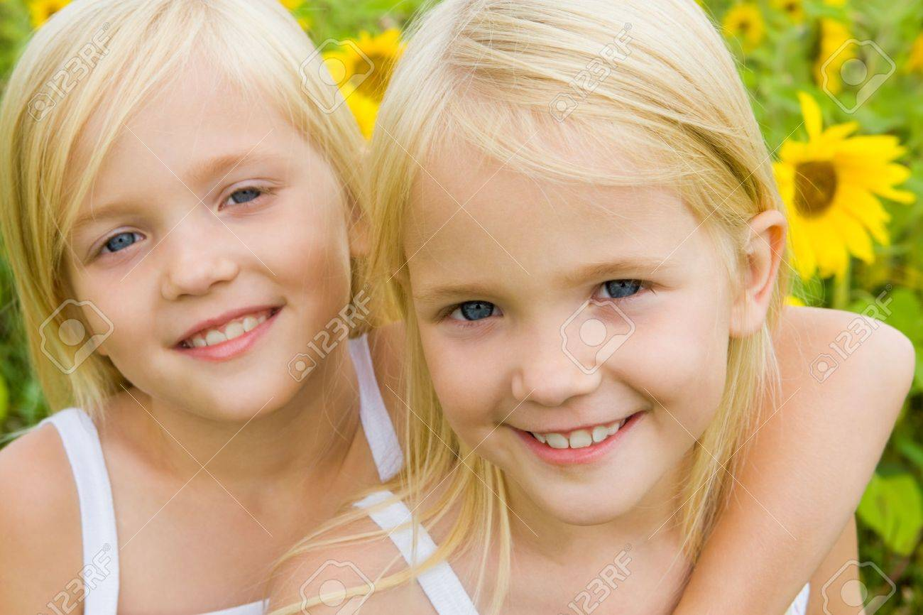 Portrait of cute girl embracing her twin sister and both looking at camera with smiles Stock Photo - 8508213