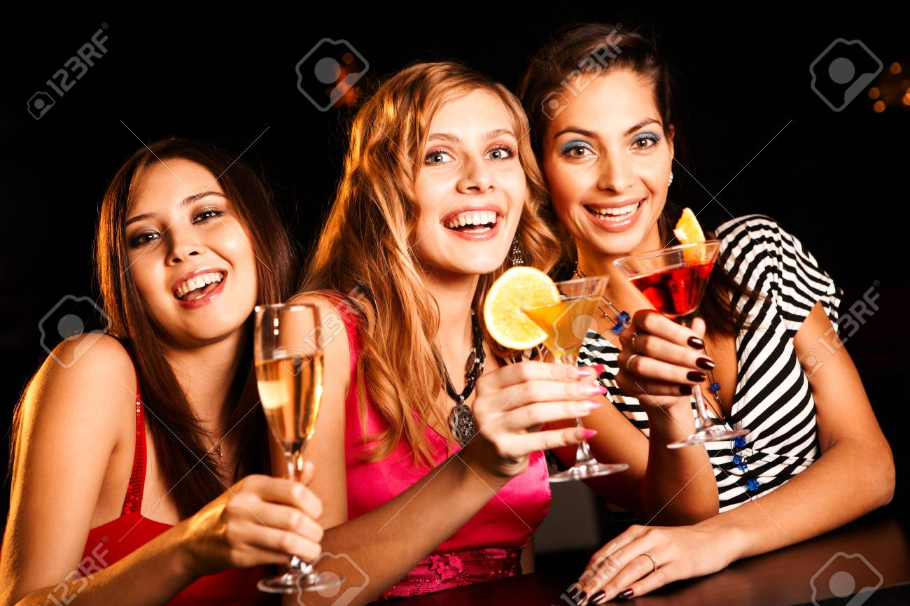 Portrait of happy girlfriends holding martini glasses with cocktails Stock Photo - 8528324