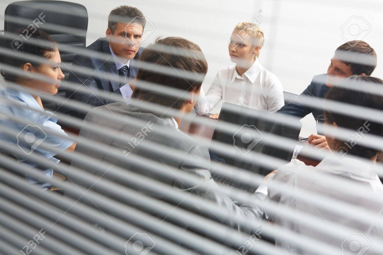 View from behind venetian blind of associates interacting at working meeting Stock Photo - 9164318