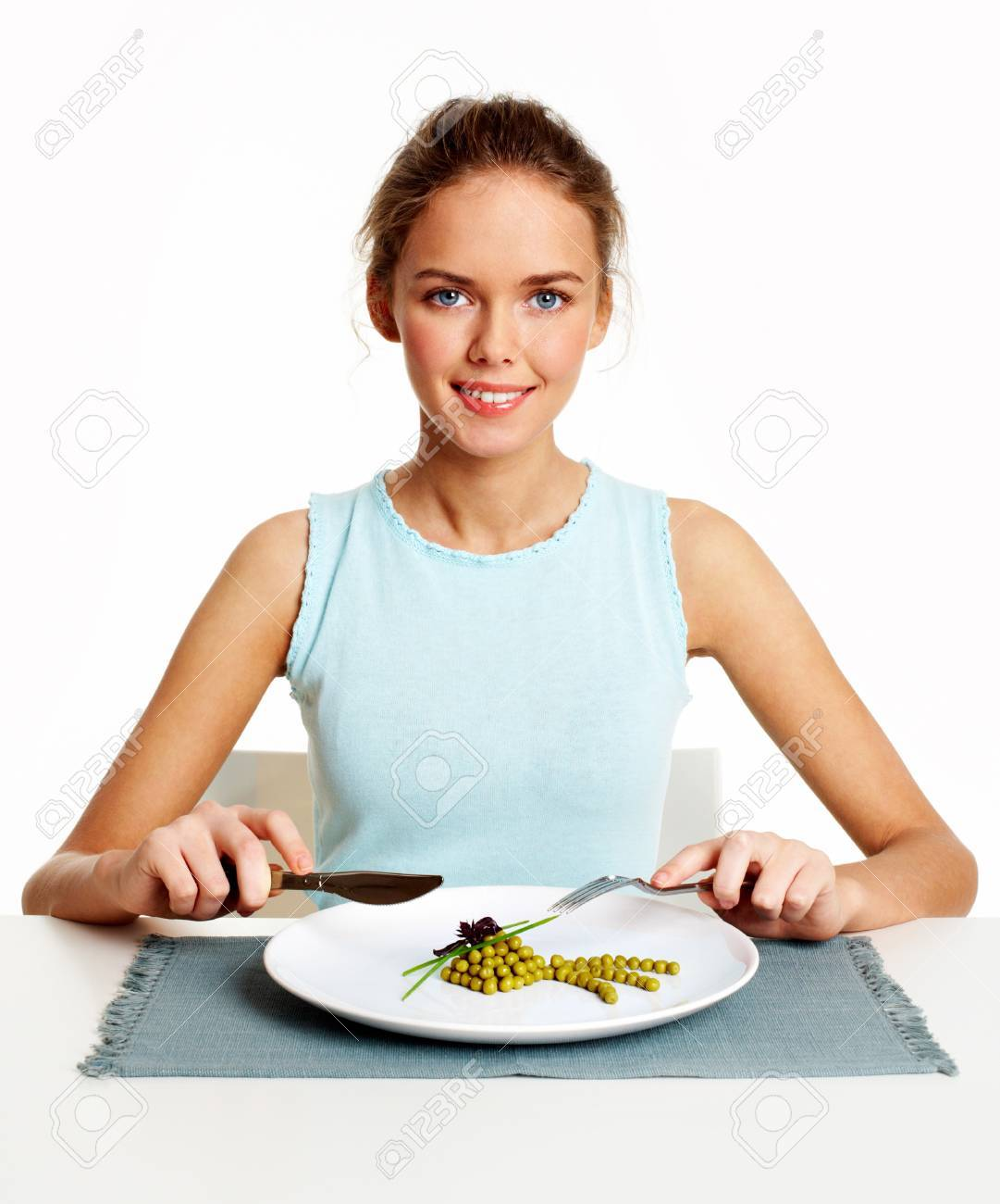 Portrait of pretty young girl with fork and knife in hands and plate with pea starter in front Stock Photo - 9164383