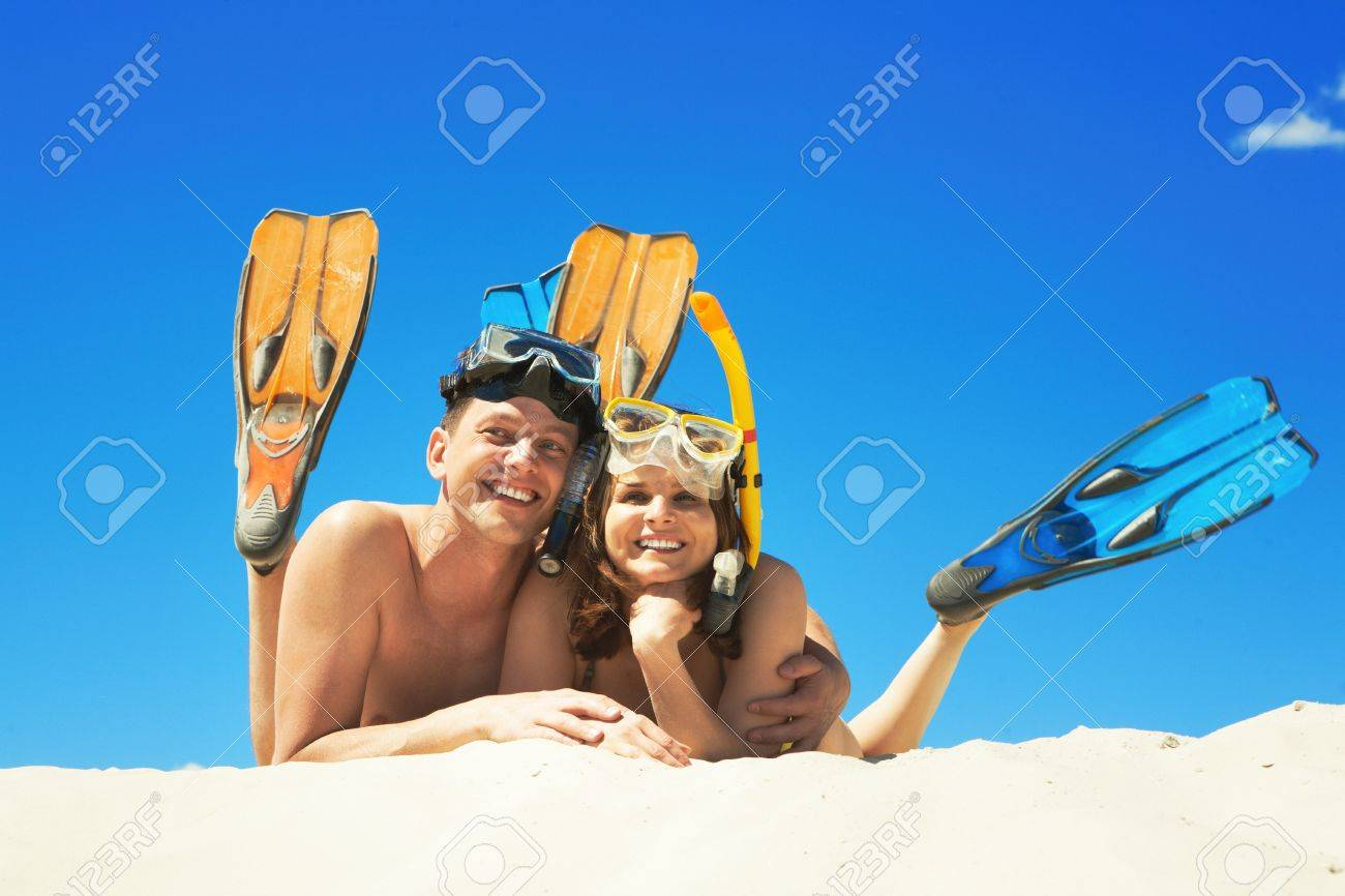 Happy family with flippers lying on sand and looking at camera Stock Photo - 9163921
