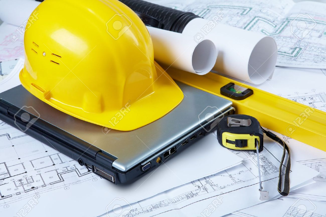 image of yellow helmet over laptop with ruler placed on blueprint