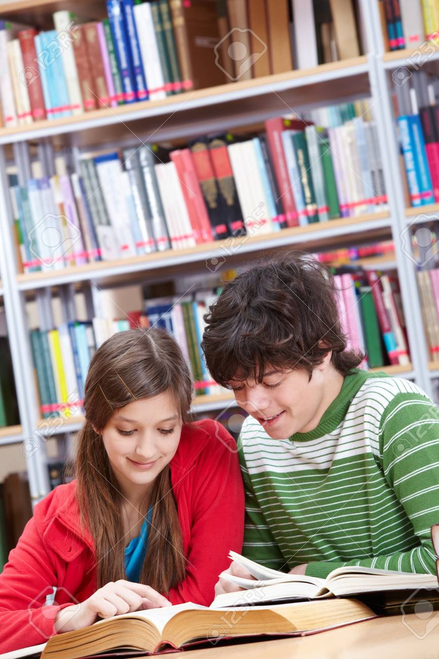Portrait of teenage girl reading book with her classmate near by Stock Photo - 9263181