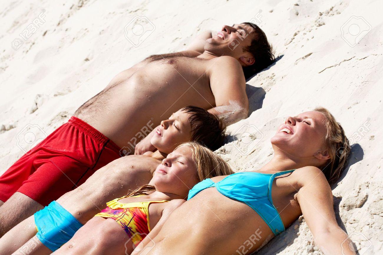 Photo of happy family lying on sand and sunbathing Stock Photo - 9298632