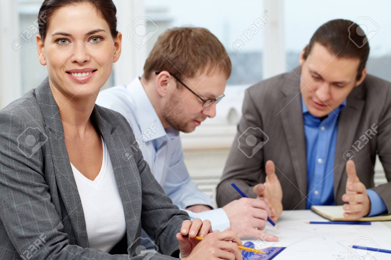 Portrait of a confident businesswoman against her working colleagues Stock Photo - 9410519