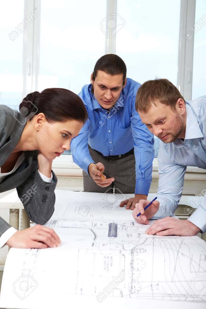 Three businesspeople examining a draft Stock Photo - 9410474