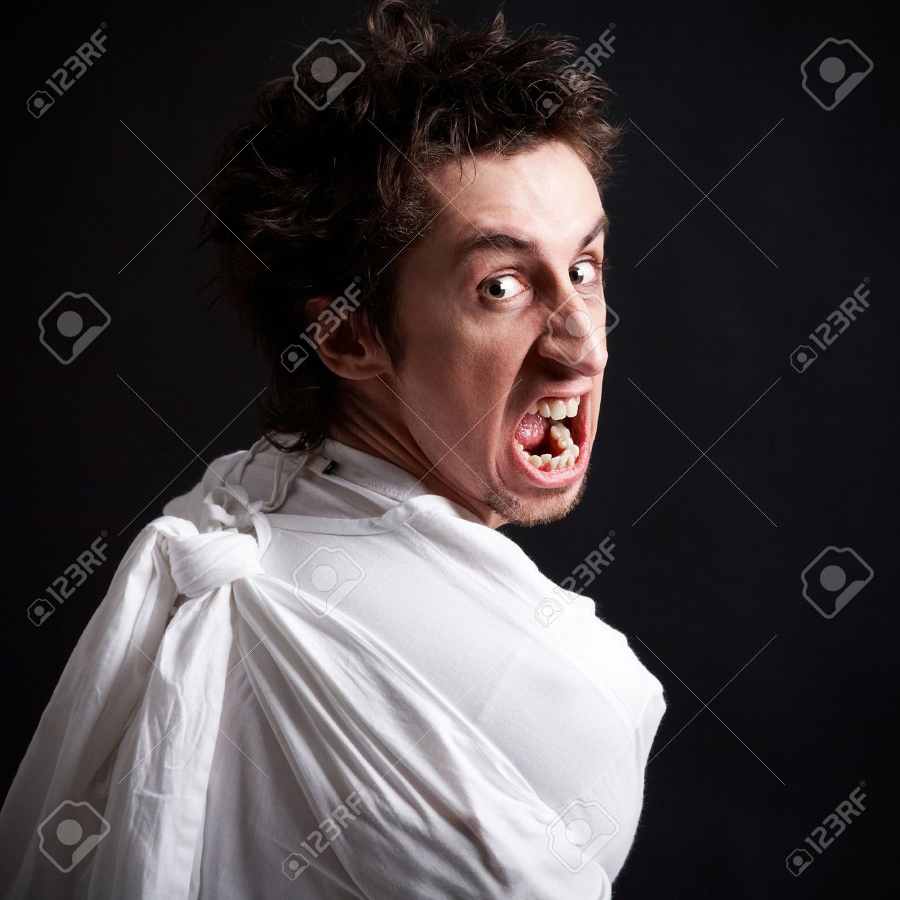 insane man in strait jacket screaming in isolation stock photo