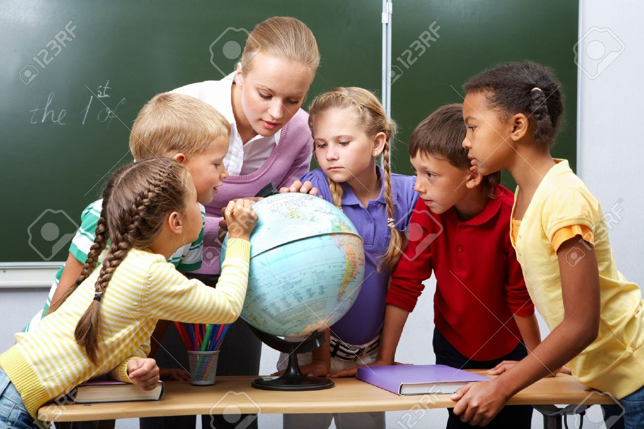 Portrait of pupils looking at globe while listening to teacher during geography lesson Stock Photo - 9437836