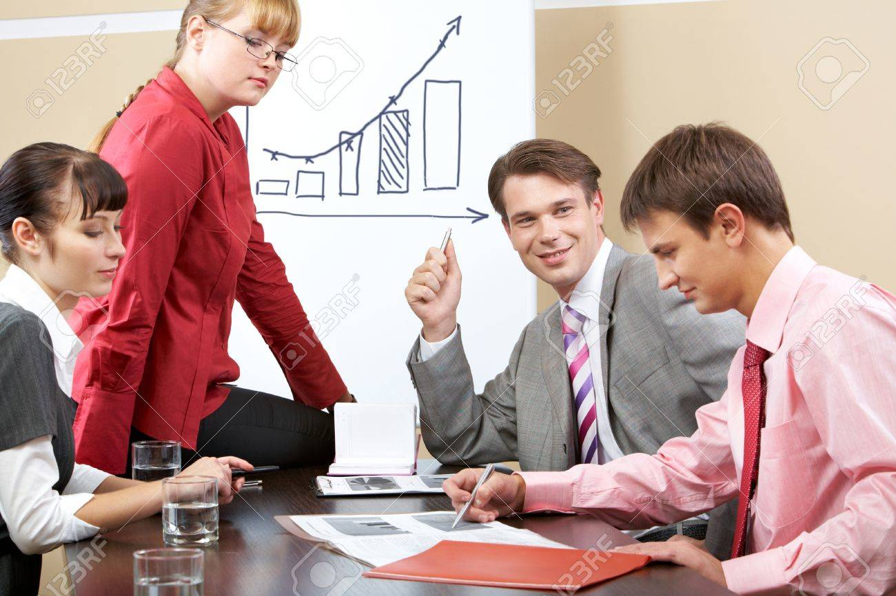 Portrait of successful team listening to young man pointing at document Stock Photo - 9634014