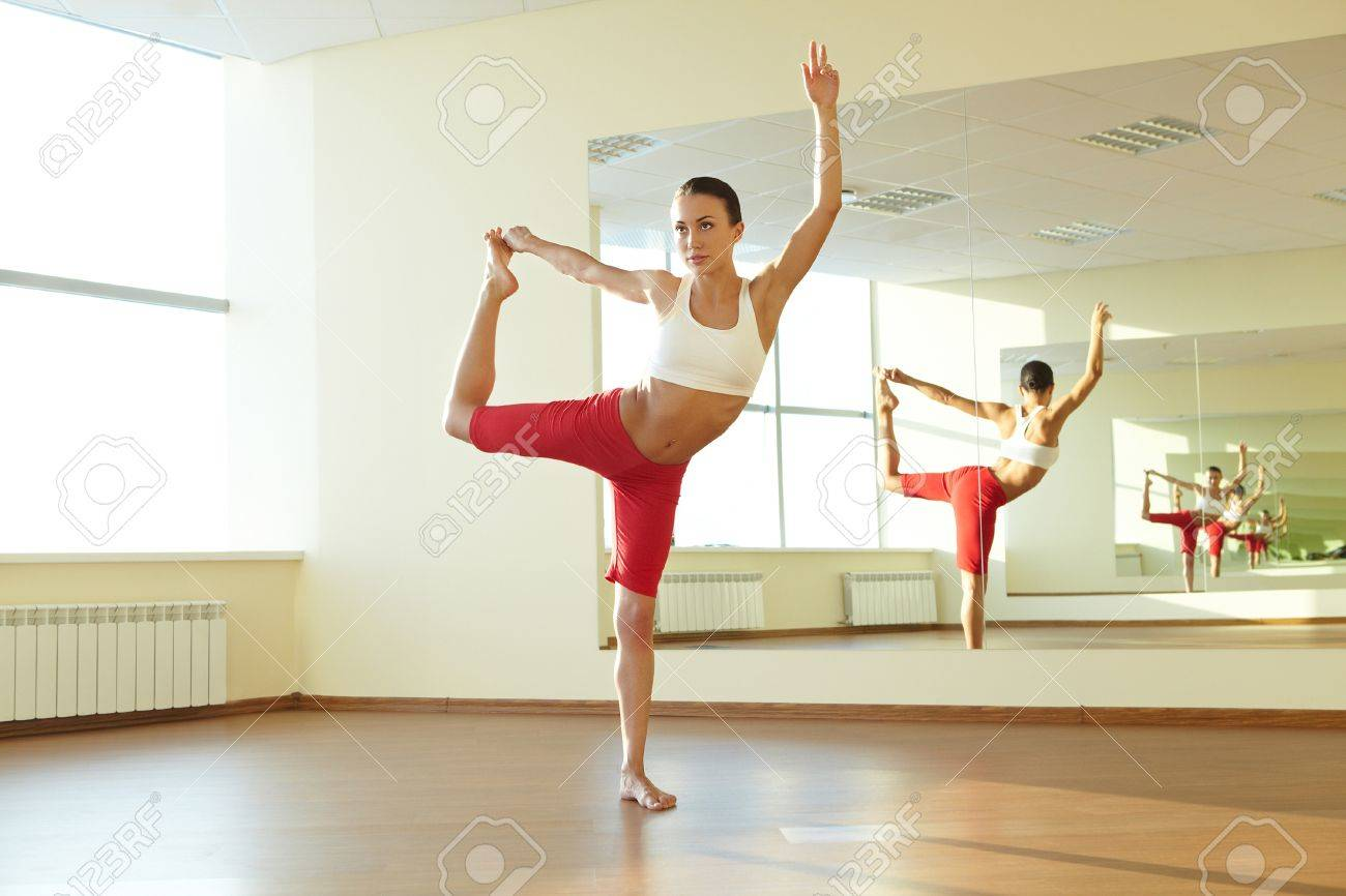 Portrait of young sporty girl doing physical exercise in front of mirror Stock Photo - 9633426