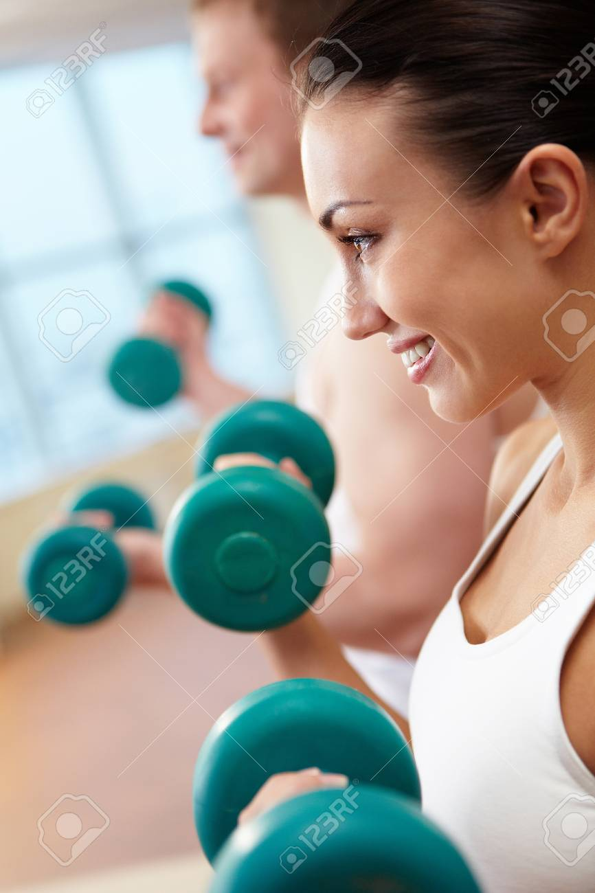 Image of smiling woman and guy doing lifting exercise with barbells in hands Stock Photo - 9633431