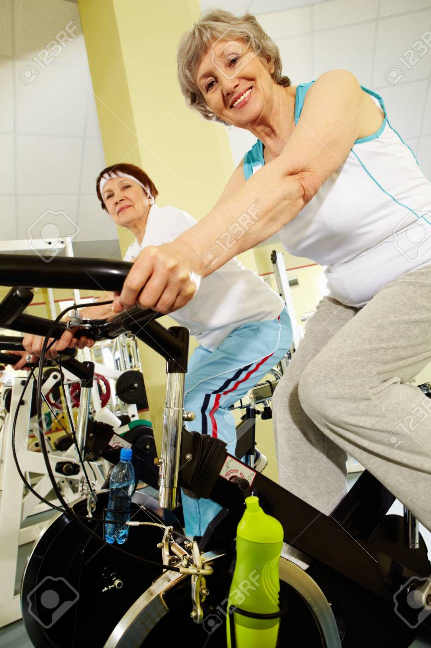Portrait of senior females doing physical exercise on special equipment in club Stock Photo - 9675401