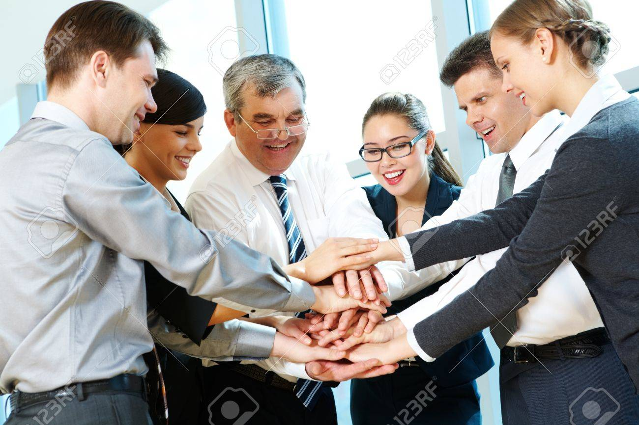 Photo of smiling co-workers making pile of hands and looking at camera Stock Photo - 9675394