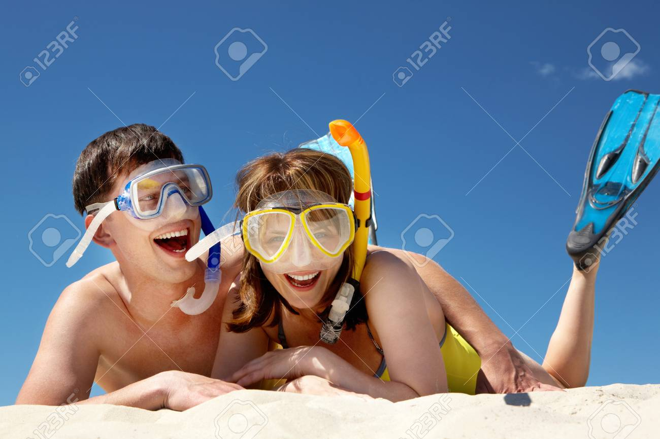 Portrait of cheerful couple in aqualungs lying on sand Stock Photo - 9725177