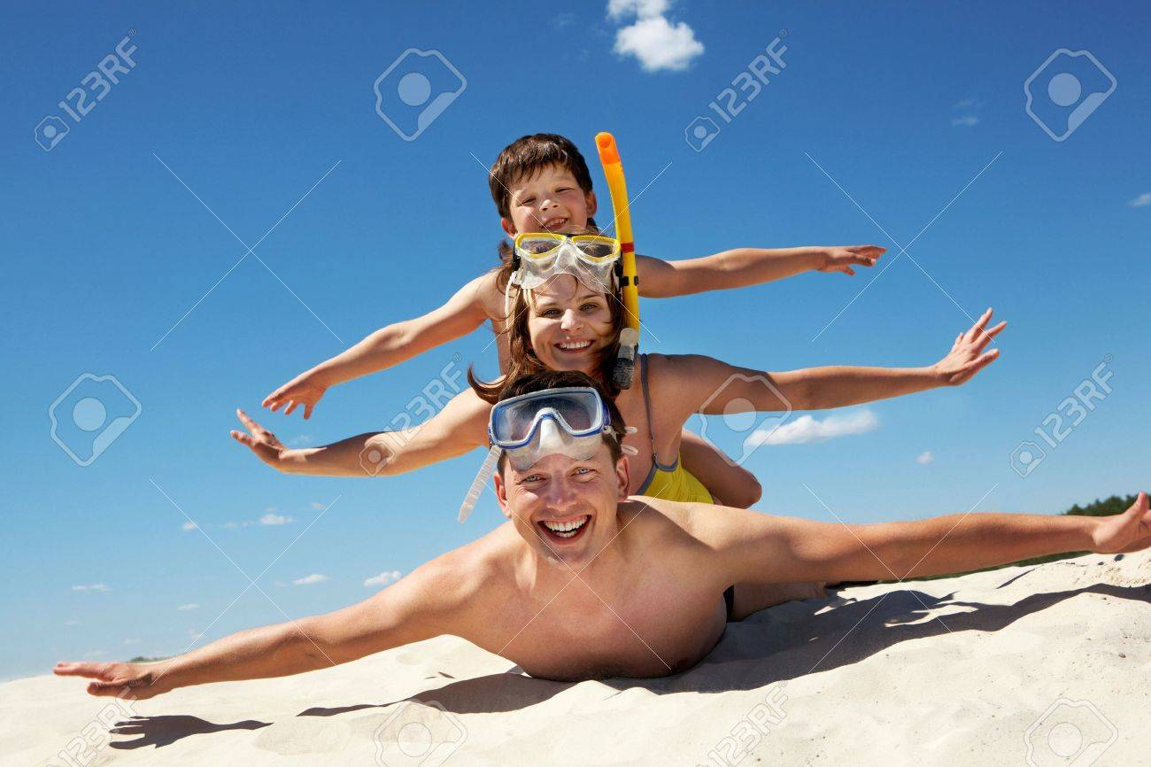 Portrait of cheerful couple and their son lying on sand and looking at camera Stock Photo - 9725138