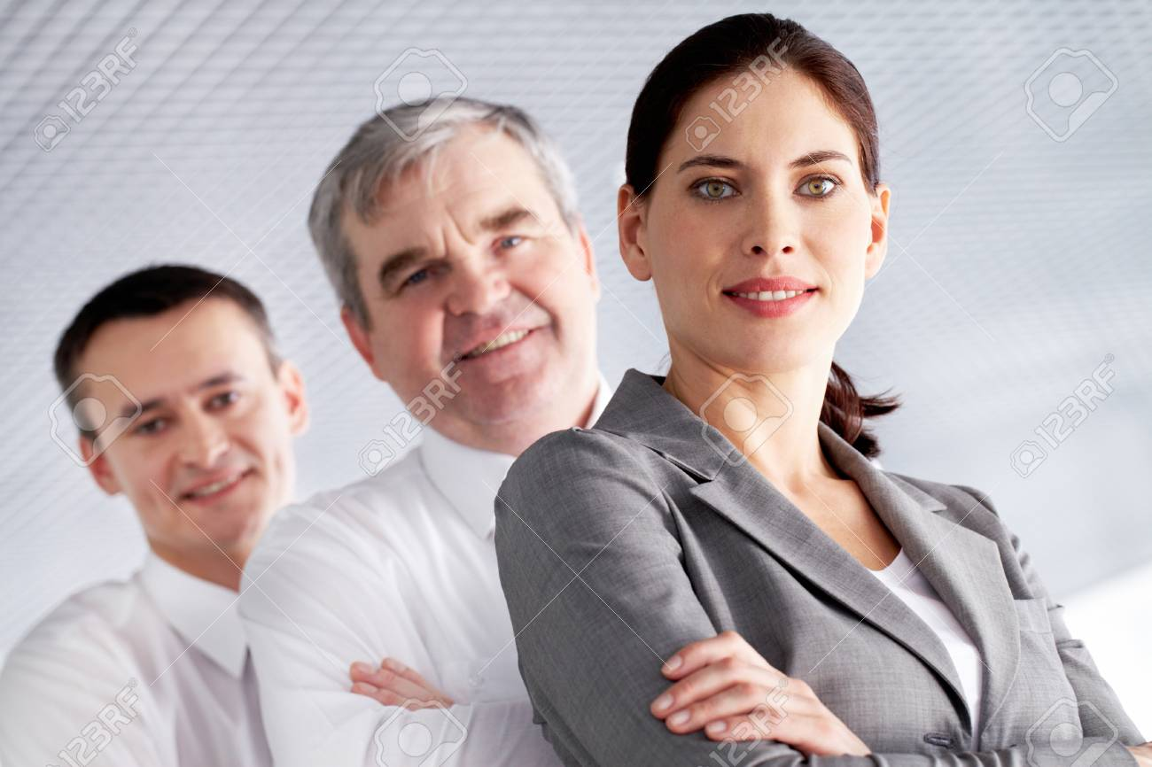 A business team with pretty leader in front looking at camera and smiling Stock Photo - 9725256