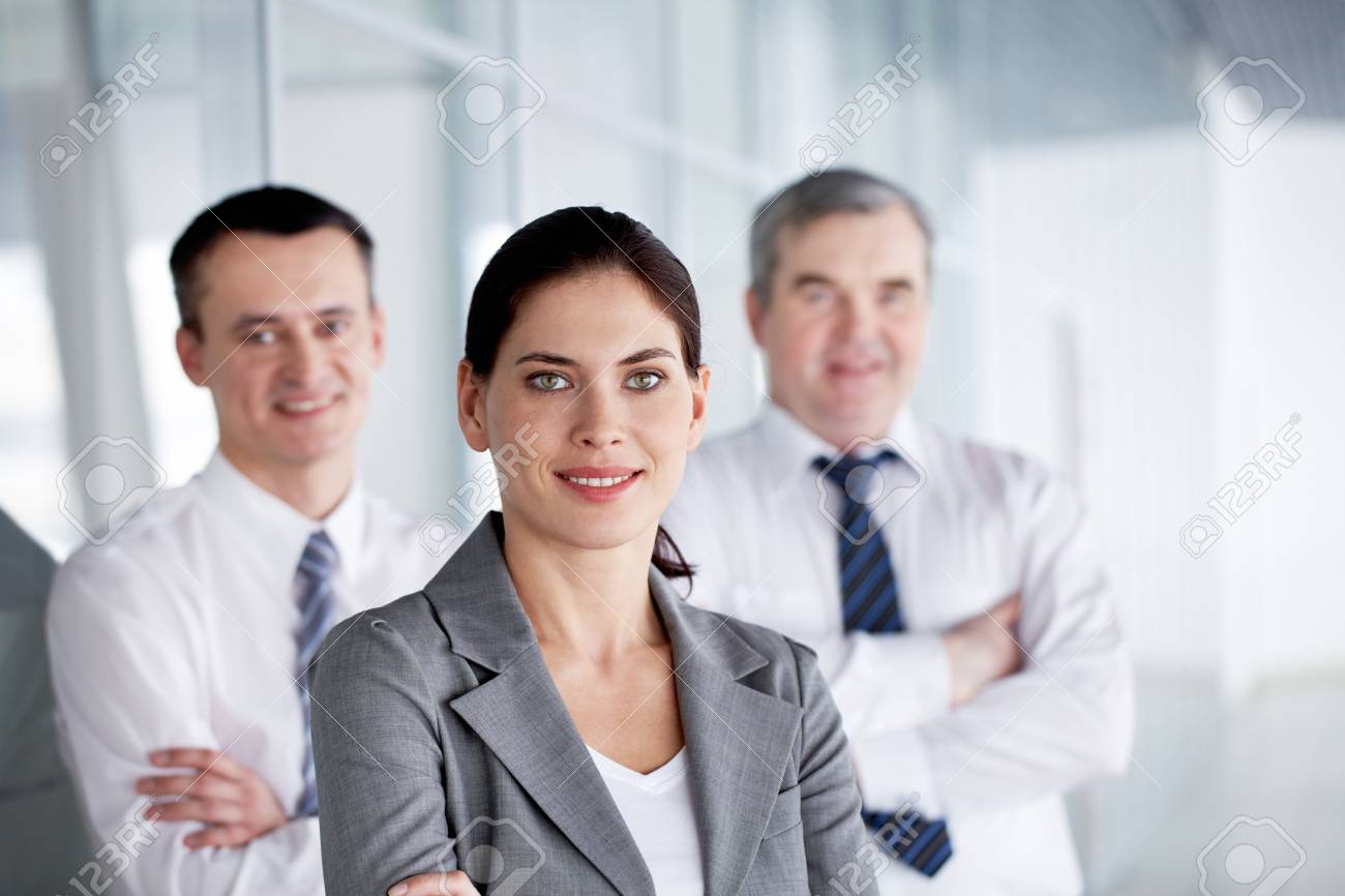 A business team with pretty leader in front looking at camera and smiling Stock Photo - 9725562
