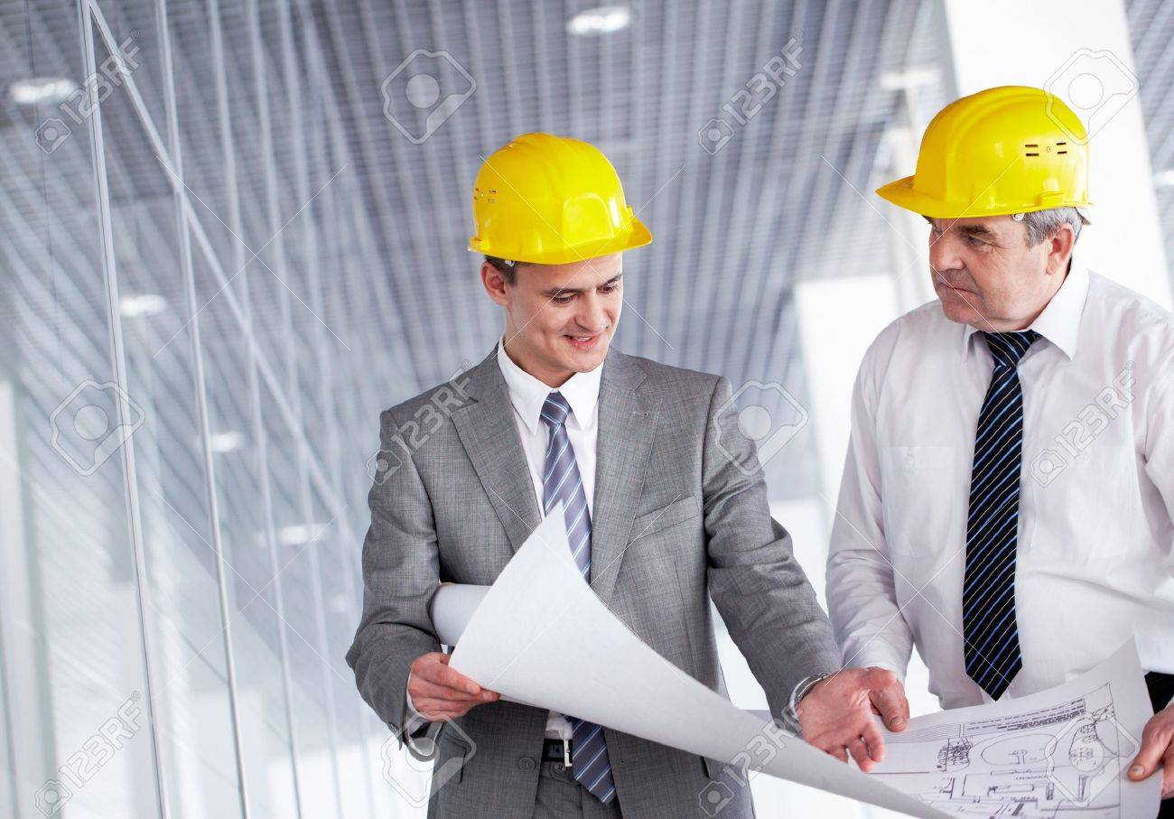 A senior leader looking at camera and smiling with colleague behind Stock Photo - 9725581