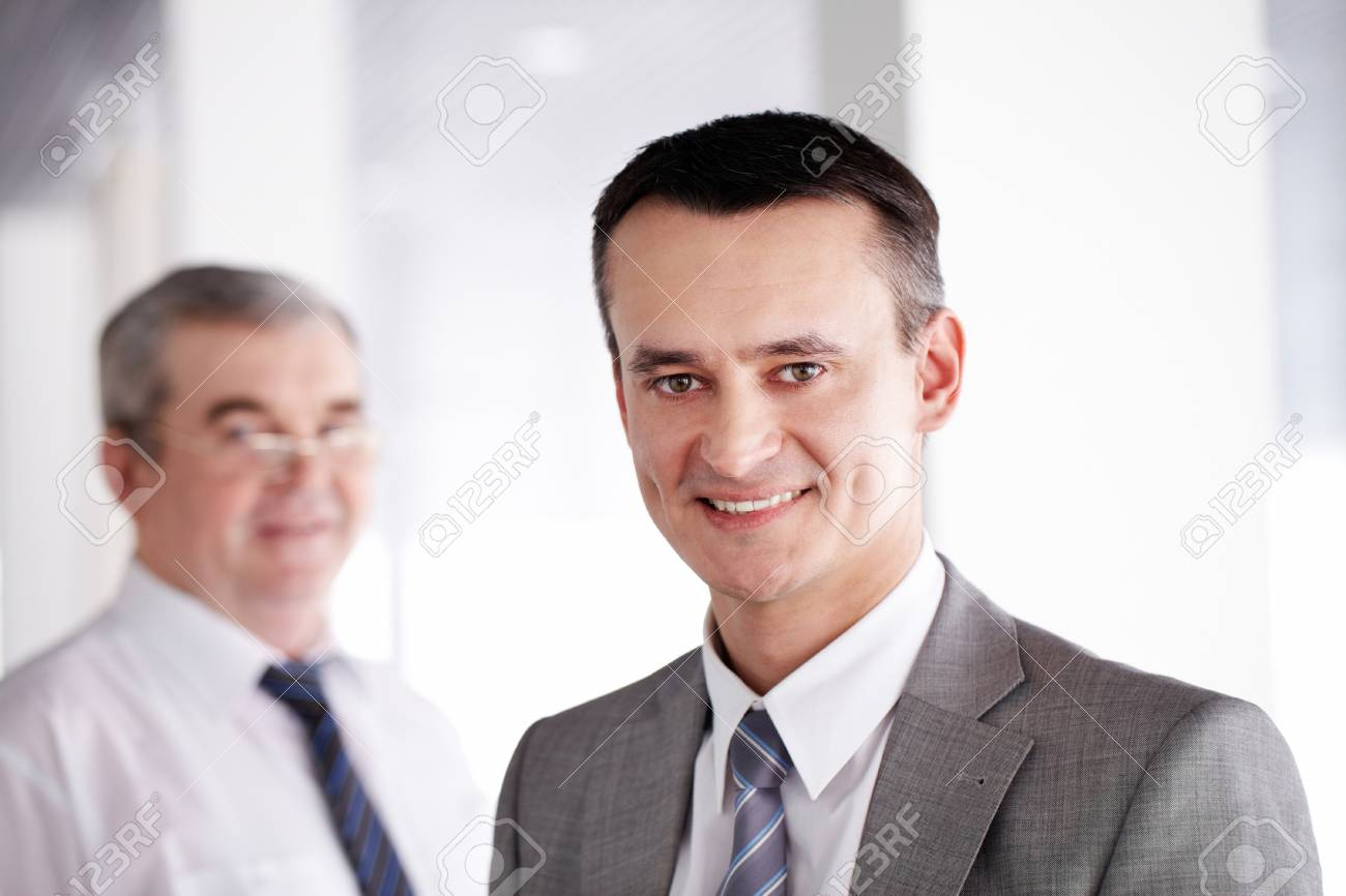 Handsome leader looking at camera and smiling with colleague behind Stock Photo - 9725242