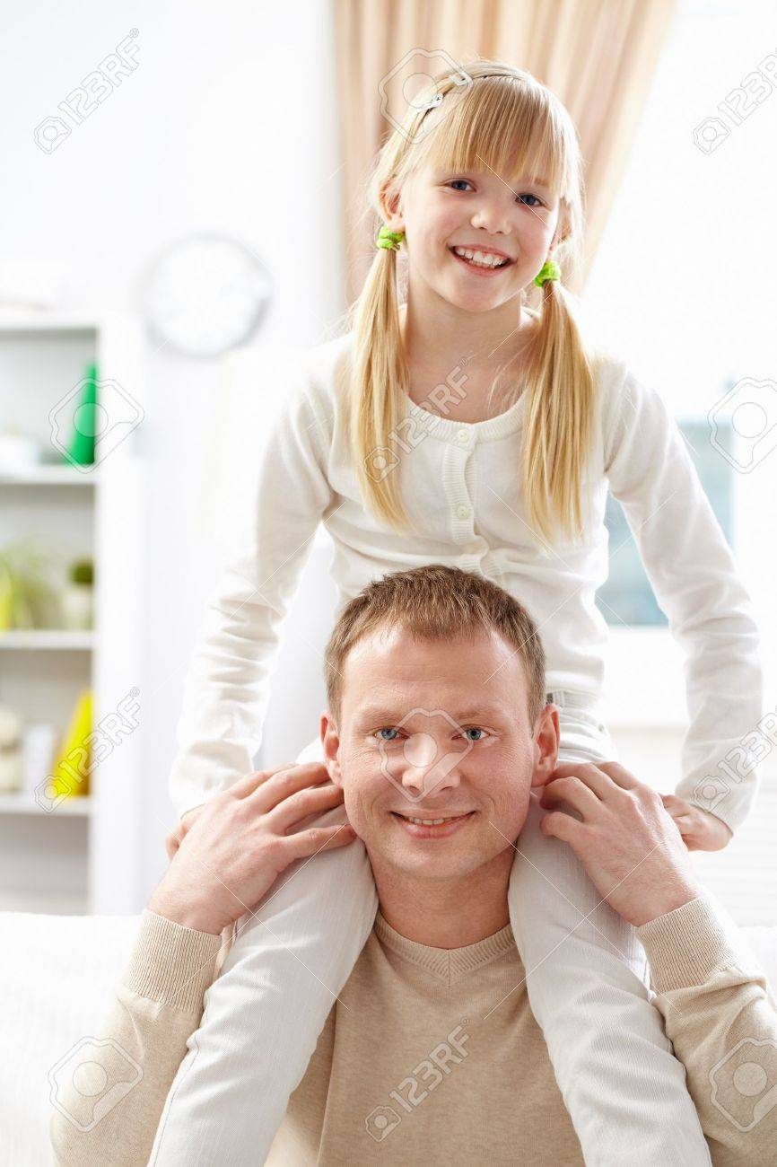 A father holds his cute daughter on shoulders Stock Photo - 9725355