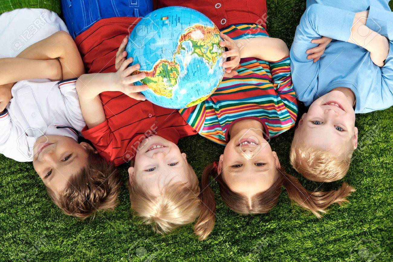 Group of happy children lying on a green grass with globe Stock Photo - 9725898