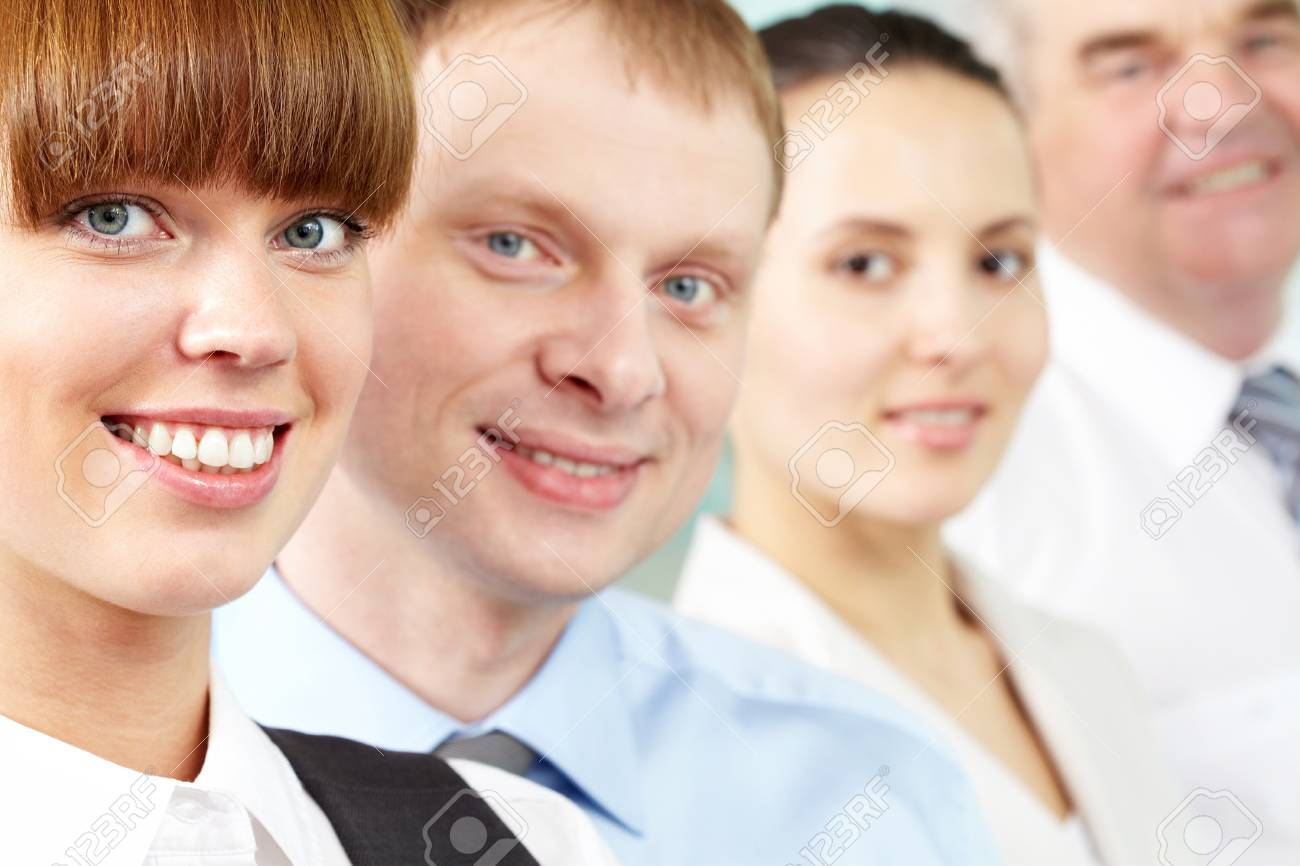 Portrait of friendly leader looking at camera with three employees behind Stock Photo - 9725748