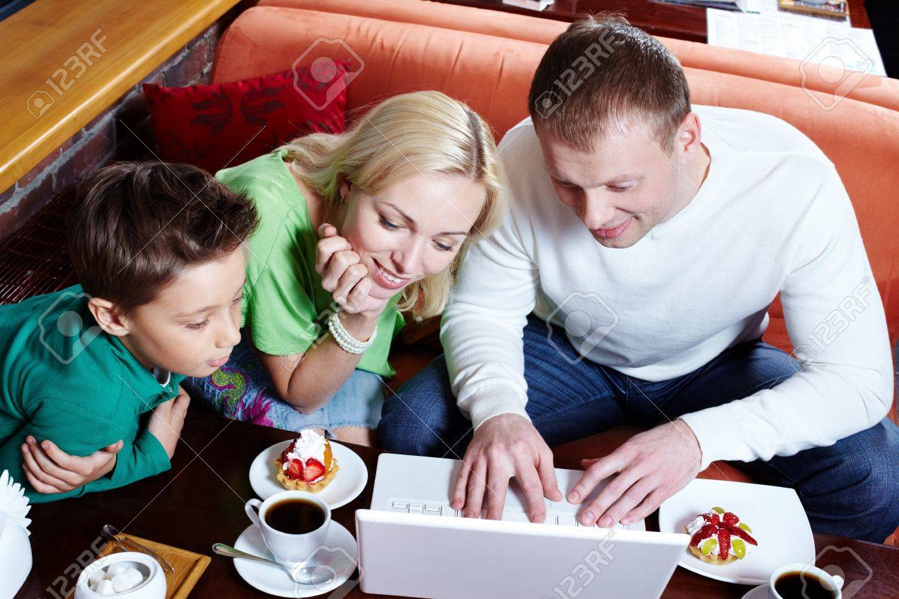Image of happy family looking at laptop screen in cafe Stock Photo - 9725860