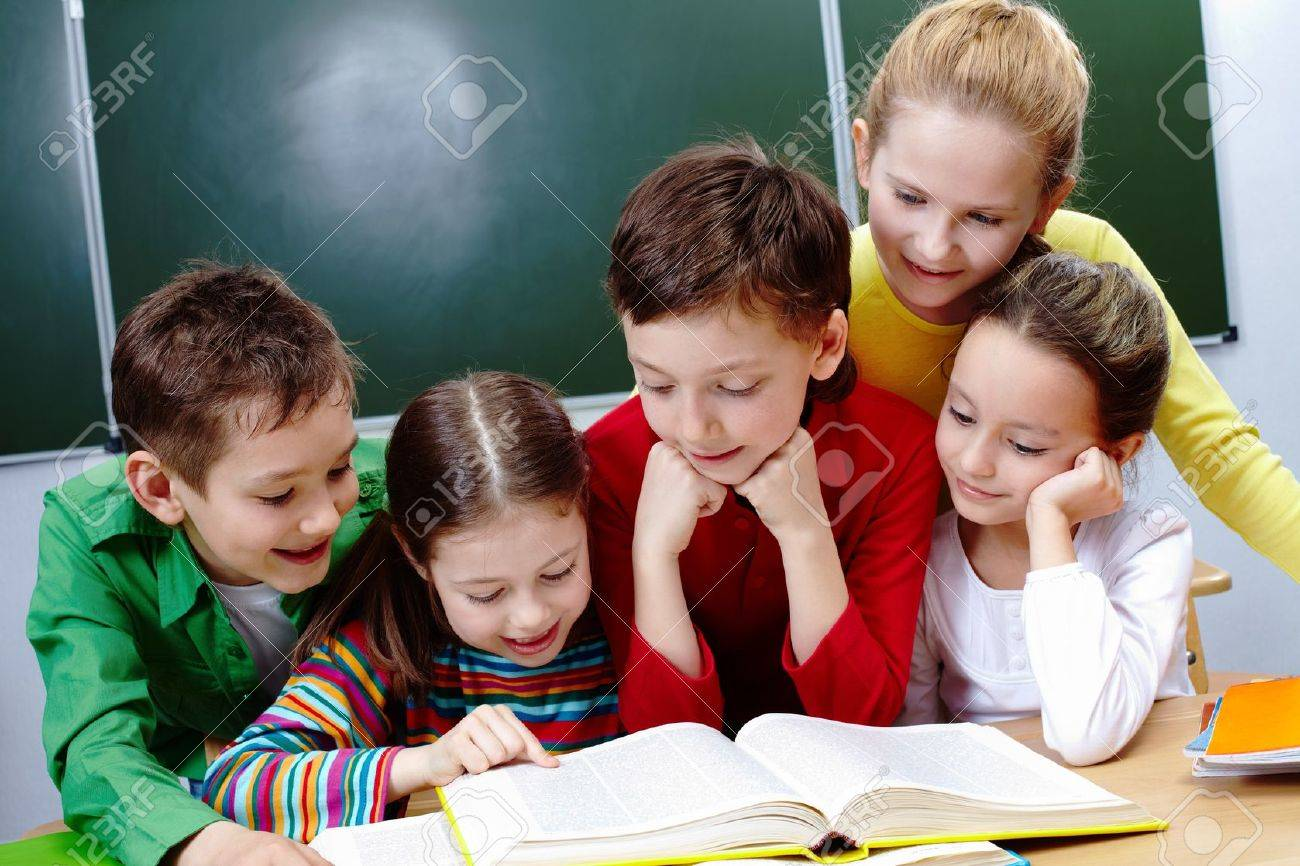 Portrait of friendly group reading book in classroom Stock Photo - 9725848