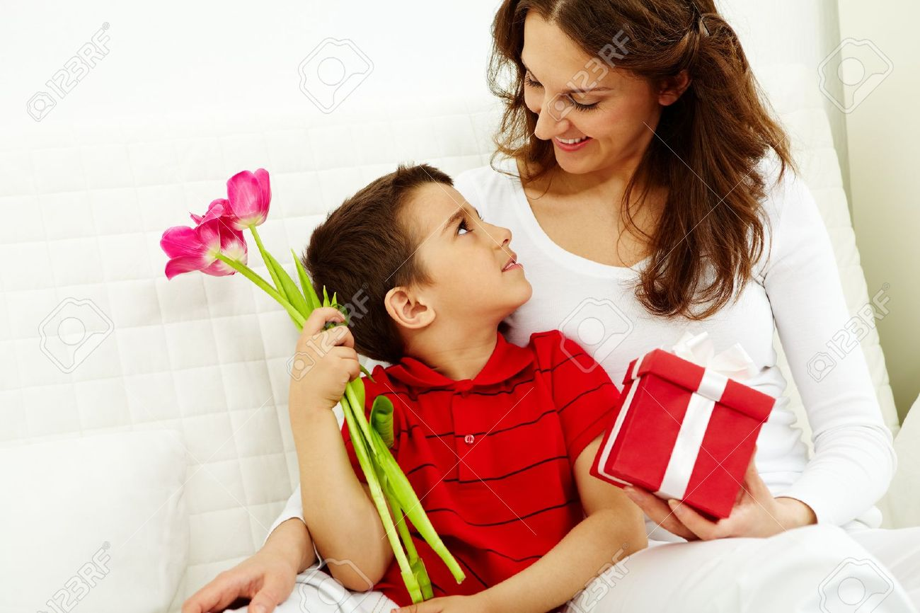Cute lad with bunch of beautiful tulips looking at his mother with giftbox Stock Photo - 9725799