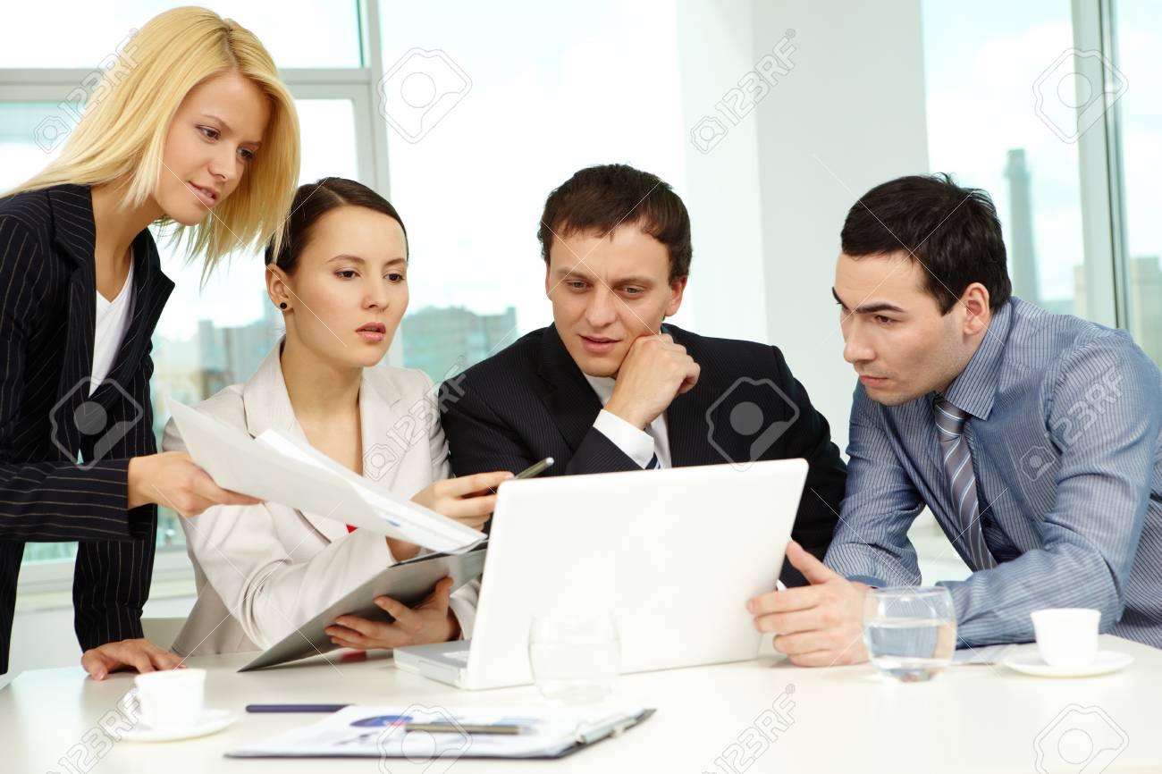 Portrait of several colleagues looking at laptop screen in office Stock Photo - 9725939