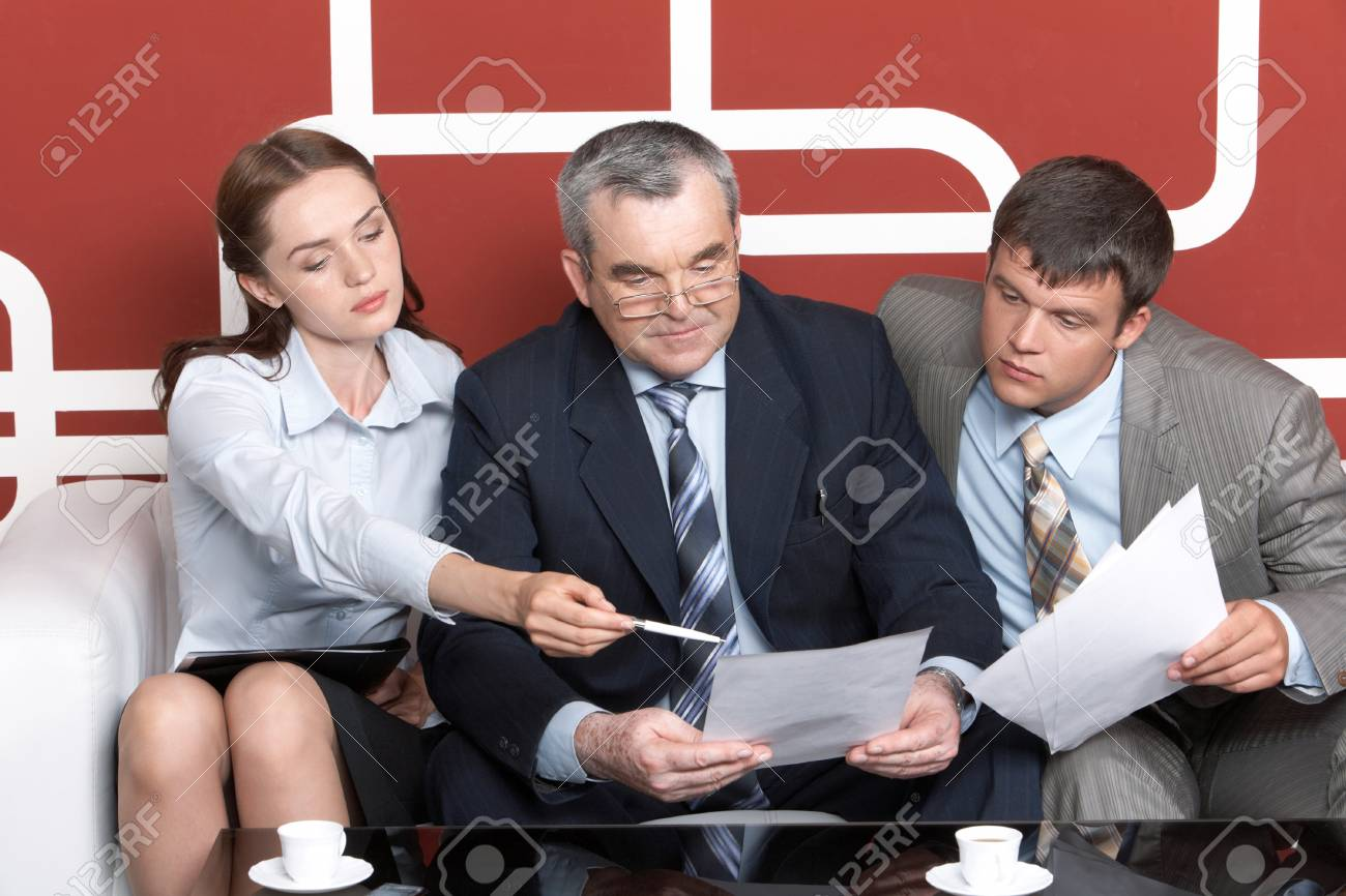 Serious men looking with interest into business plan in chief�s hands at which pretty woman pointing while sitting on sofa Stock Photo - 9726363