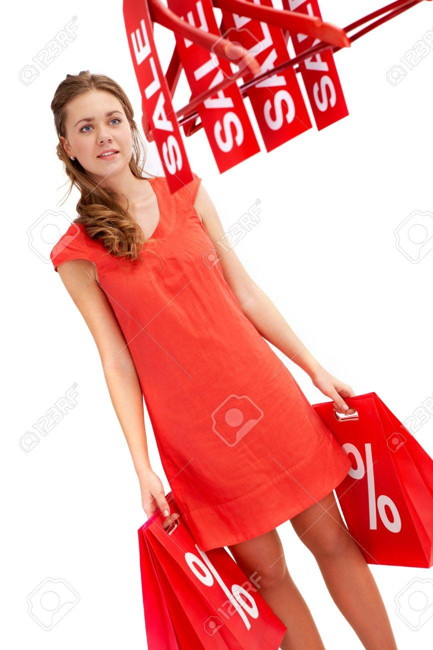 Young shopper carrying bags and looking at hangers with discount symbols Stock Photo - 9726359