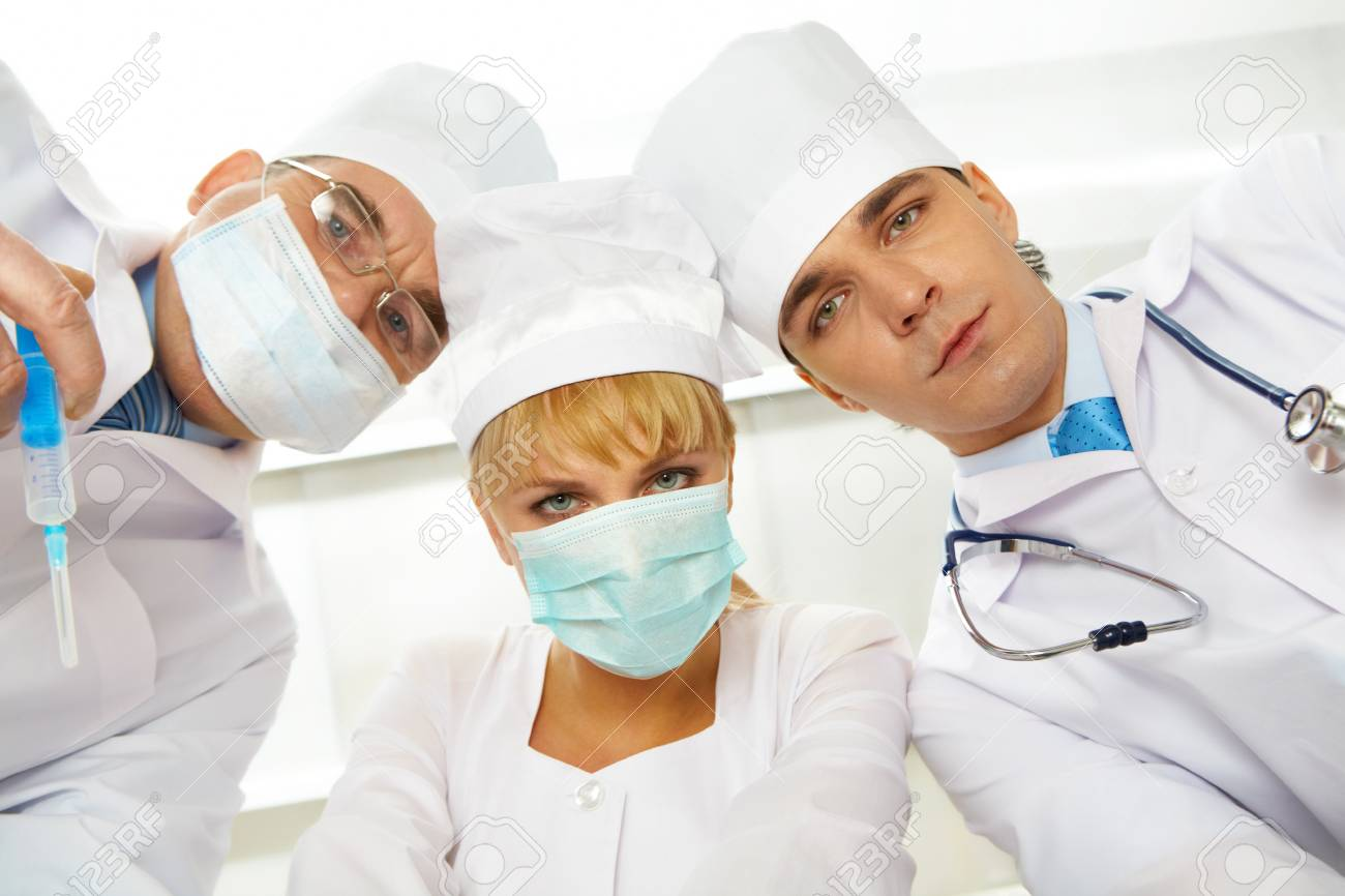 Three serious therapeutists touching their heads while looking at camera Stock Photo - 9726552