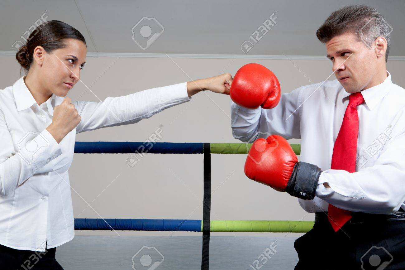 Portrait of aggressive businessman in boxing gloves fighting with serious female Stock Photo - 9727167