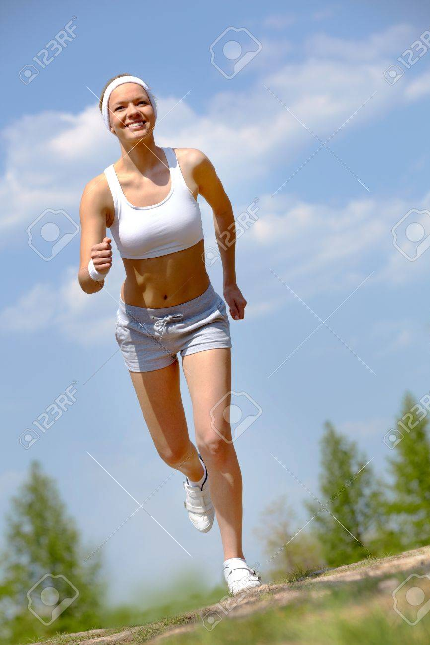 Portrait of happy young woman jogging outside Stock Photo - 9807104