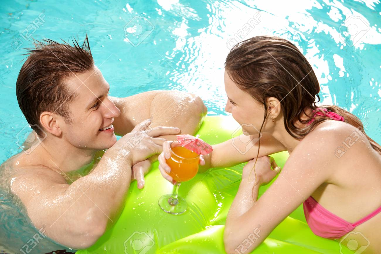 Handsome guy and pretty girl looking at one another in swimming pool Stock Photo - 9805144