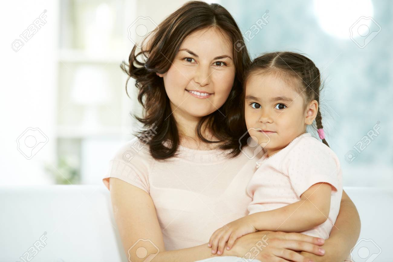 Portrait of happy mother holding her daughter and both looking at camera Stock Photo - 9817829