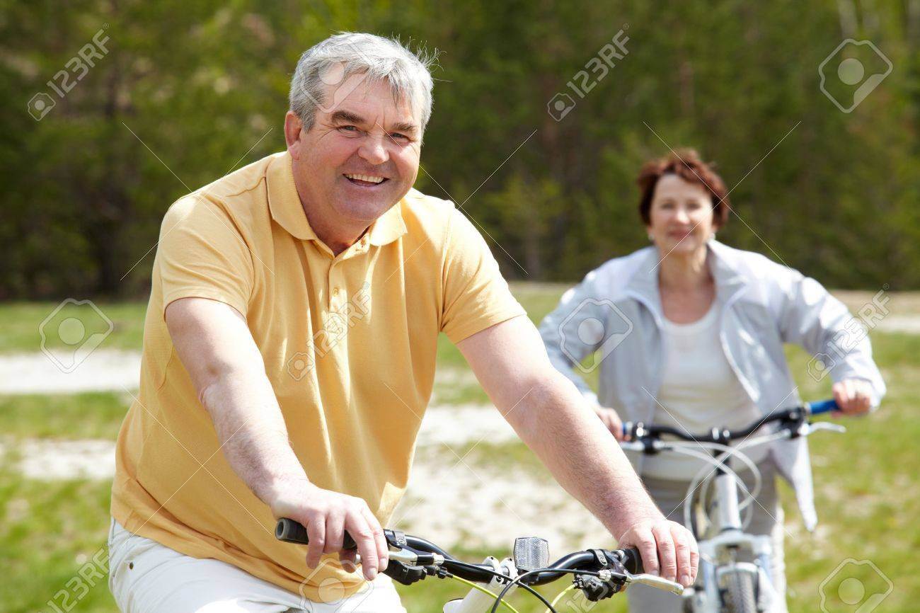 Portrait of happy mature man on bicycle with senior woman on background Stock Photo - 9819159