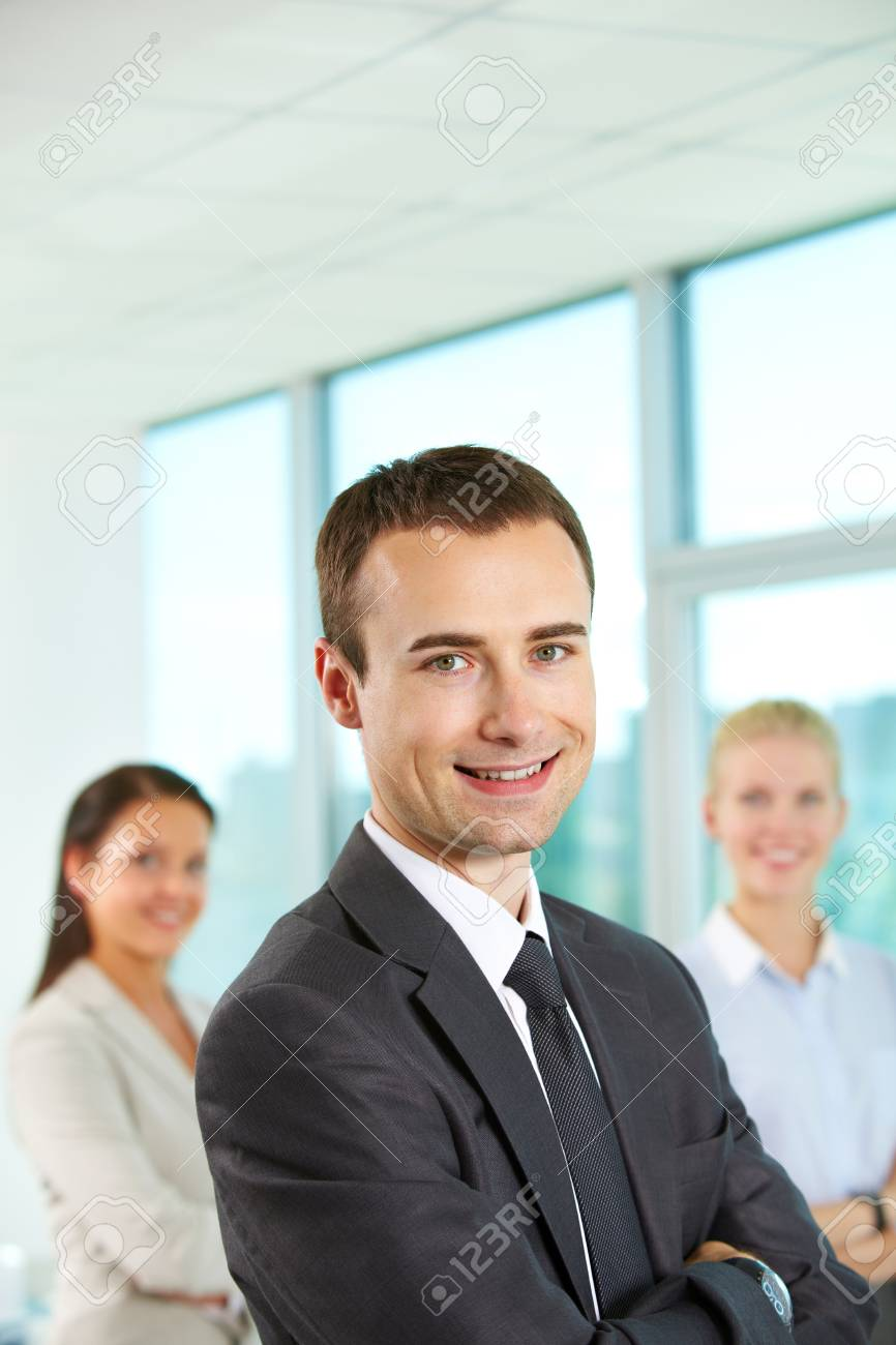Portrait of friendly leader looking at camera with two employees behind Stock Photo - 9818454