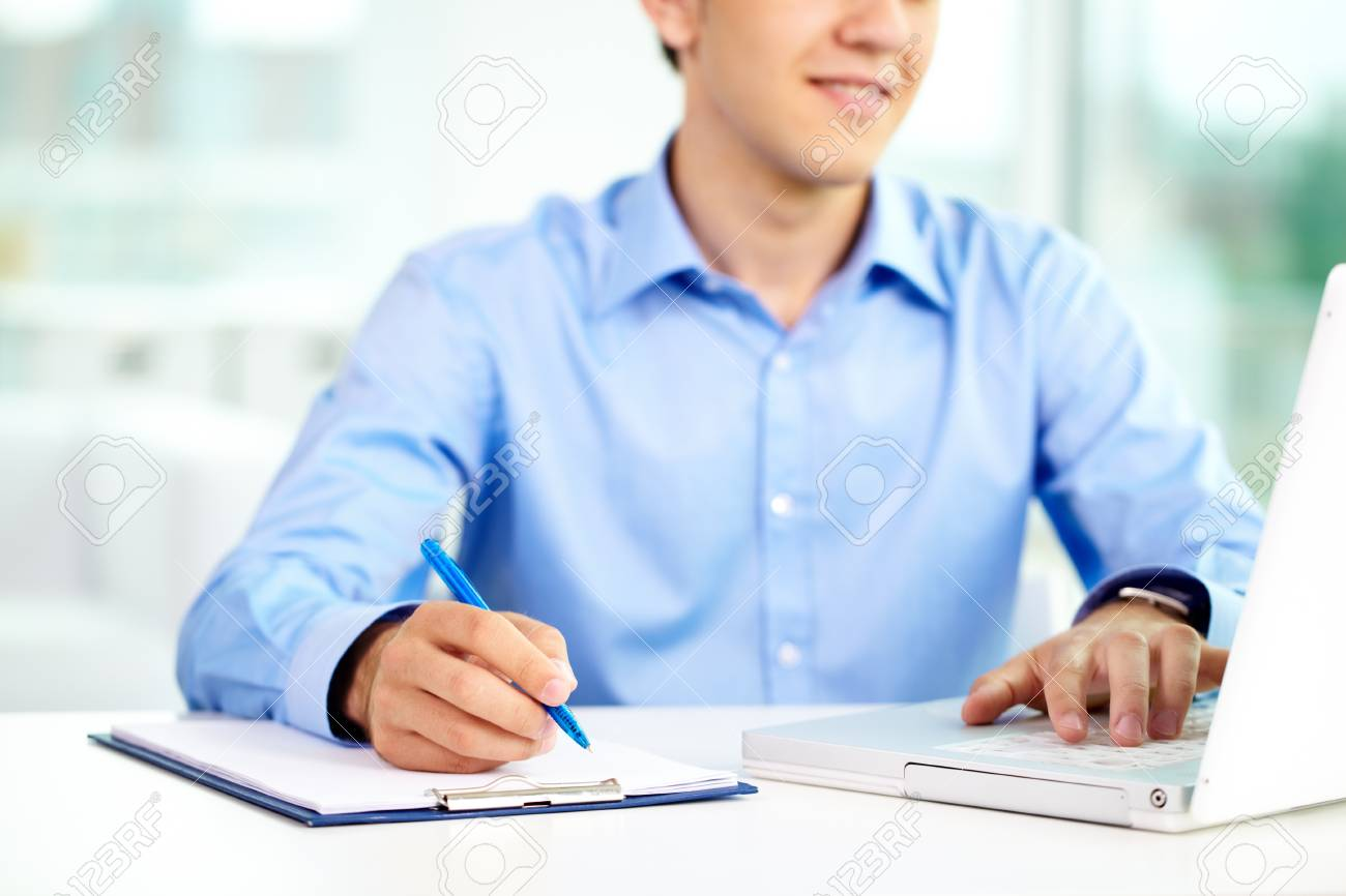Image of successful businessman typing and making notes Stock Photo - 9910461