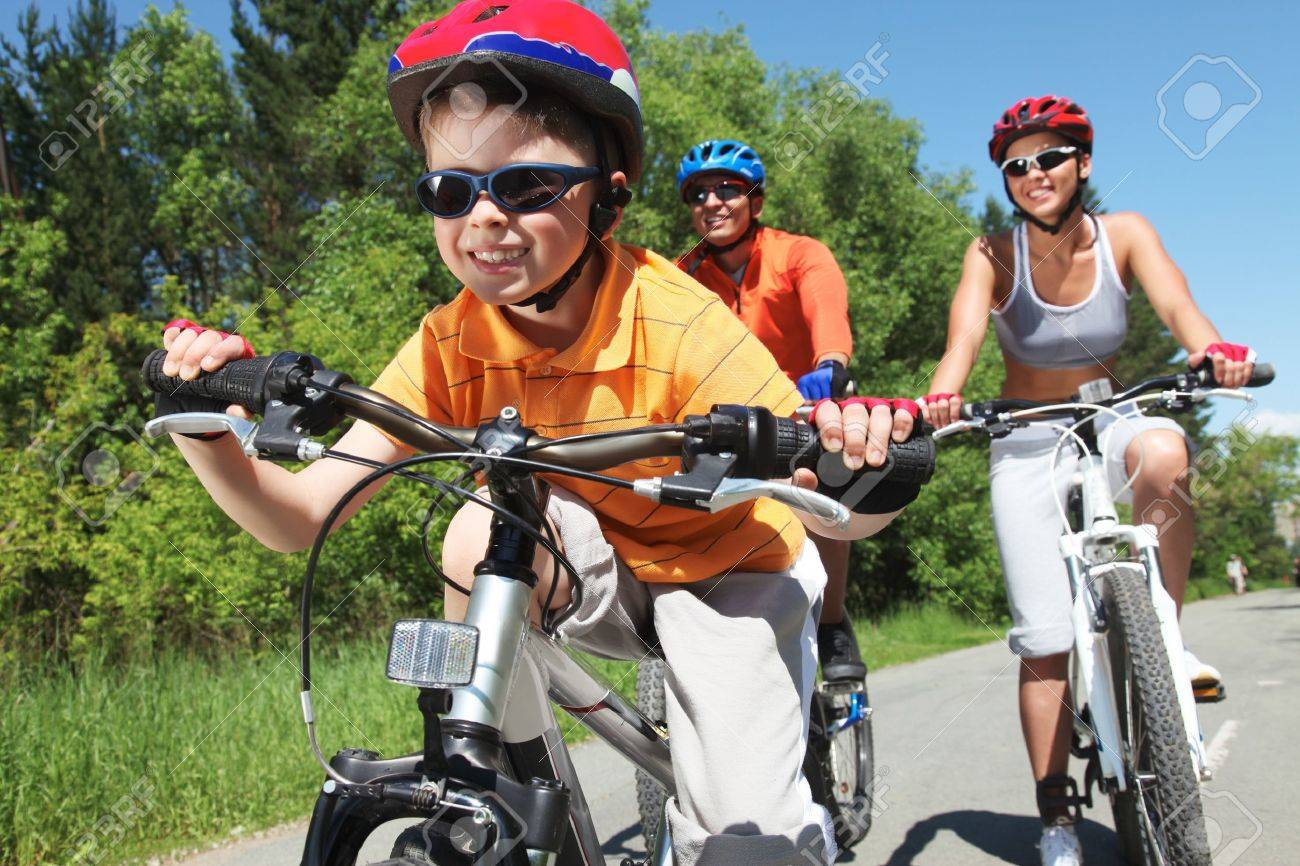 Portrait of happy boy riding bicycle in the park with his parents behind Stock Photo - 9910525