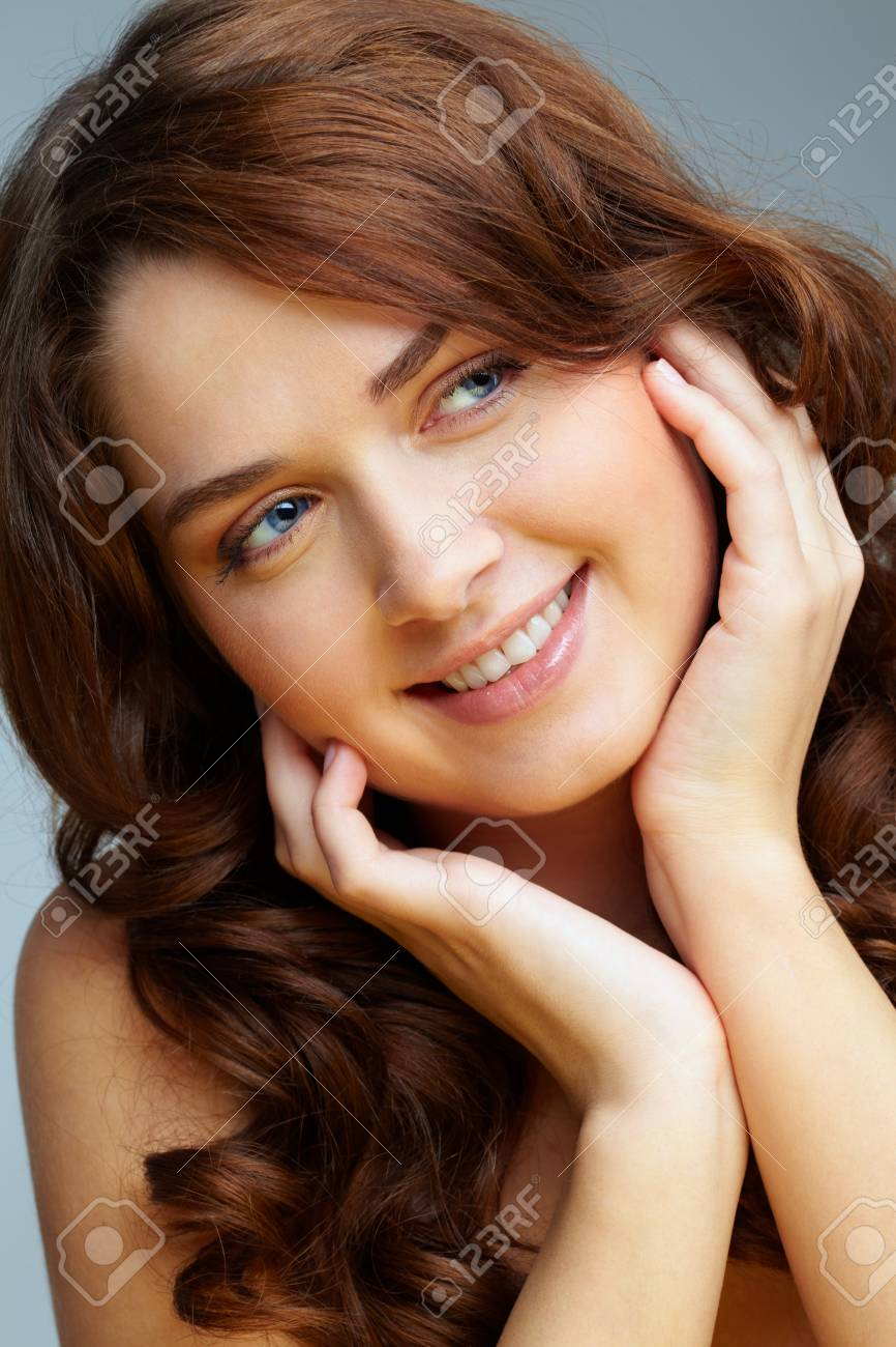 Portrait of charming girl touching her face and looking aside Stock Photo - 9910689