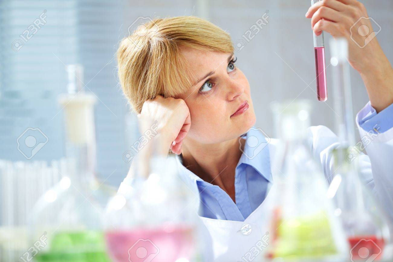 A young chemist looking pensively at tubing with liquid Stock Photo - 9908792