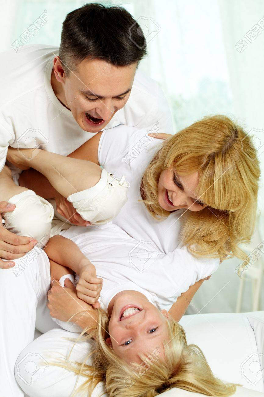 Portrait of happy parents playing with their daughter at home Stock Photo - 10068423