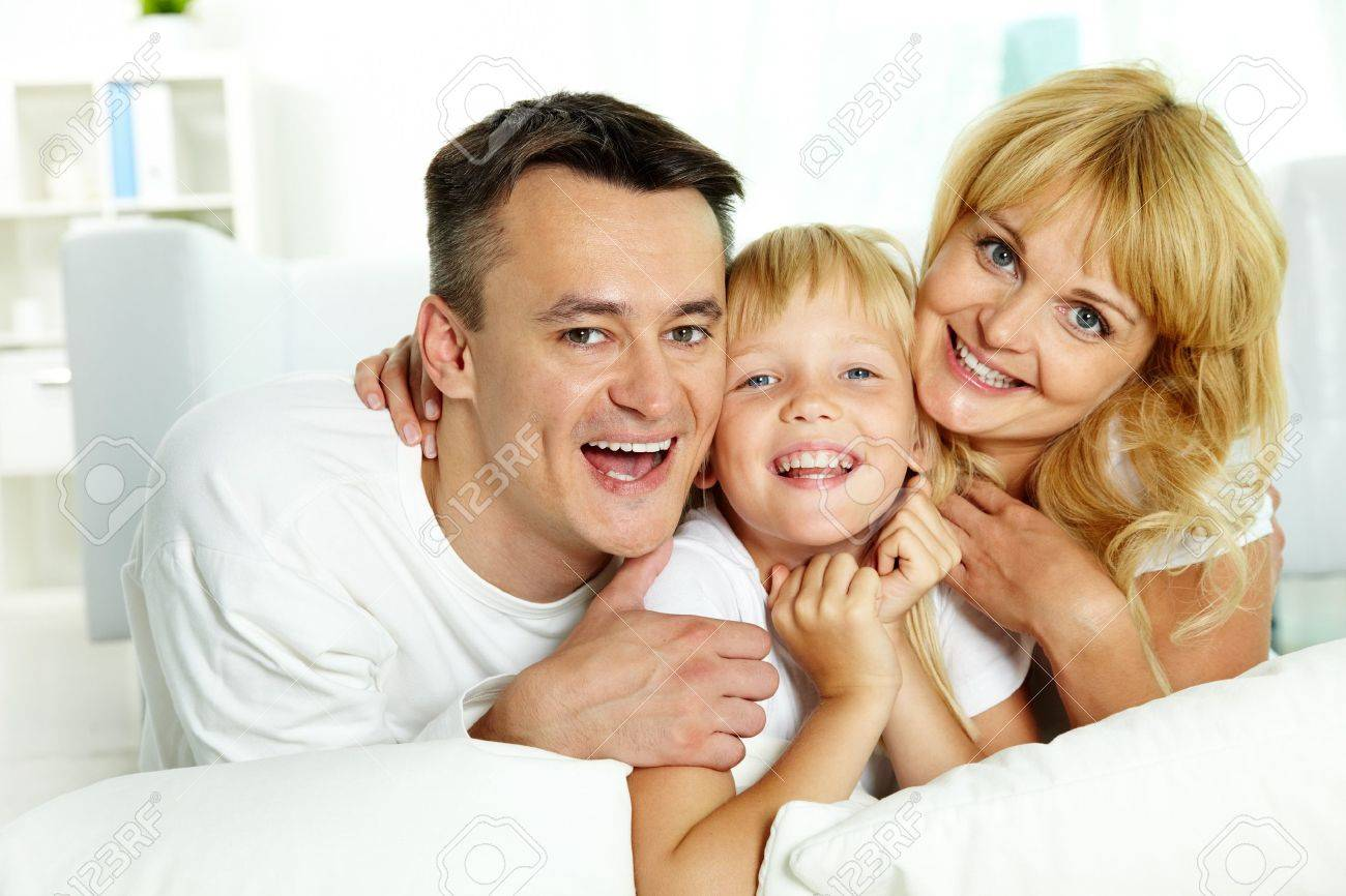 Portrait of happy parents with their daughter looking at camera at home Stock Photo - 10068504
