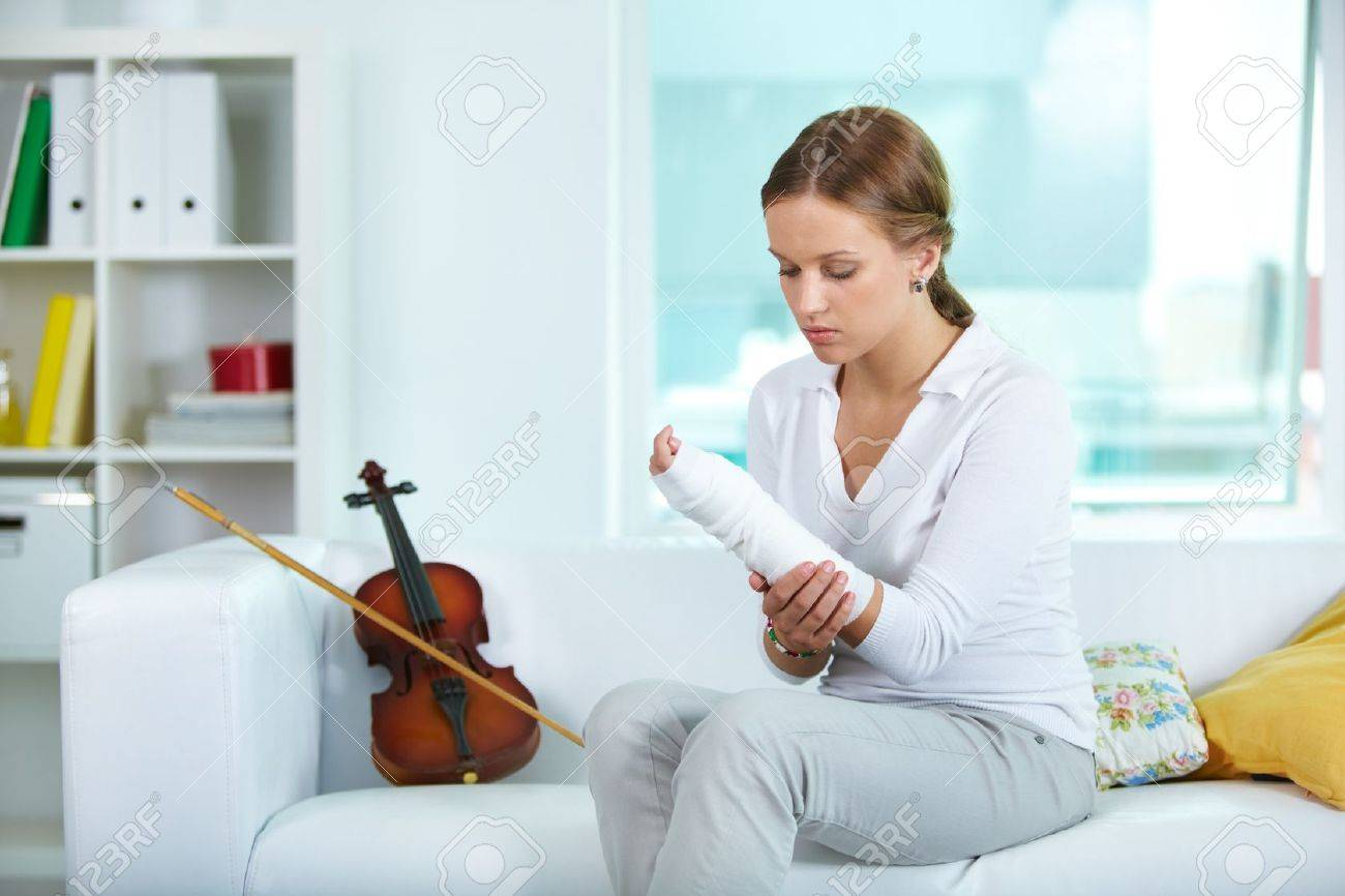Portrait of a young violinist touching her broken arm Stock Photo - 10068815
