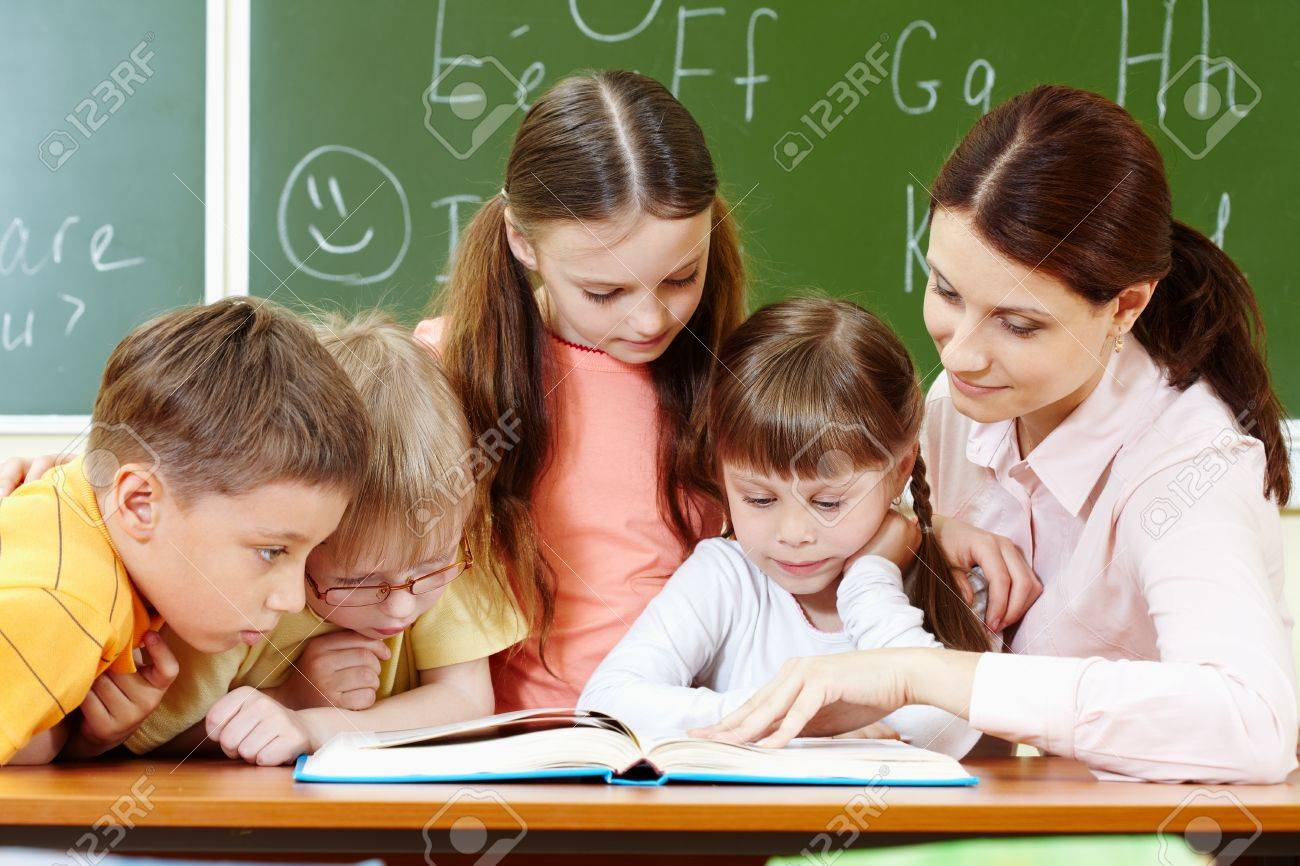 Portrait of smart schoolchildren and their teacher reading book in classroom Stock Photo - 10122244