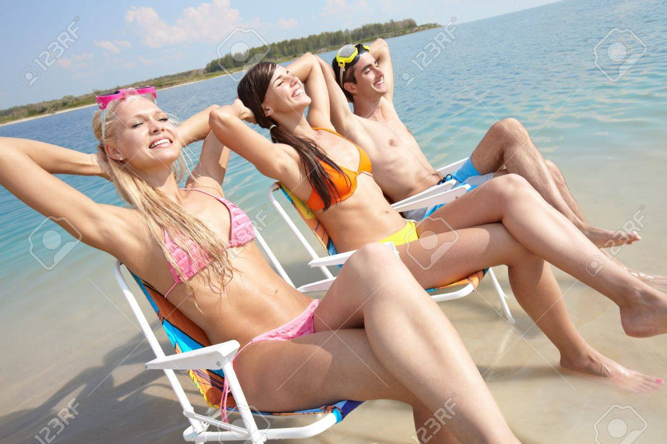 Portrait of three friends resting in chairs on the beach Stock Photo - 10130654