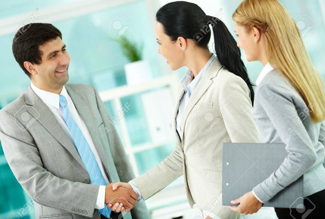 Portrait of successful associates handshaking after striking deal Stock Photo - 10203470