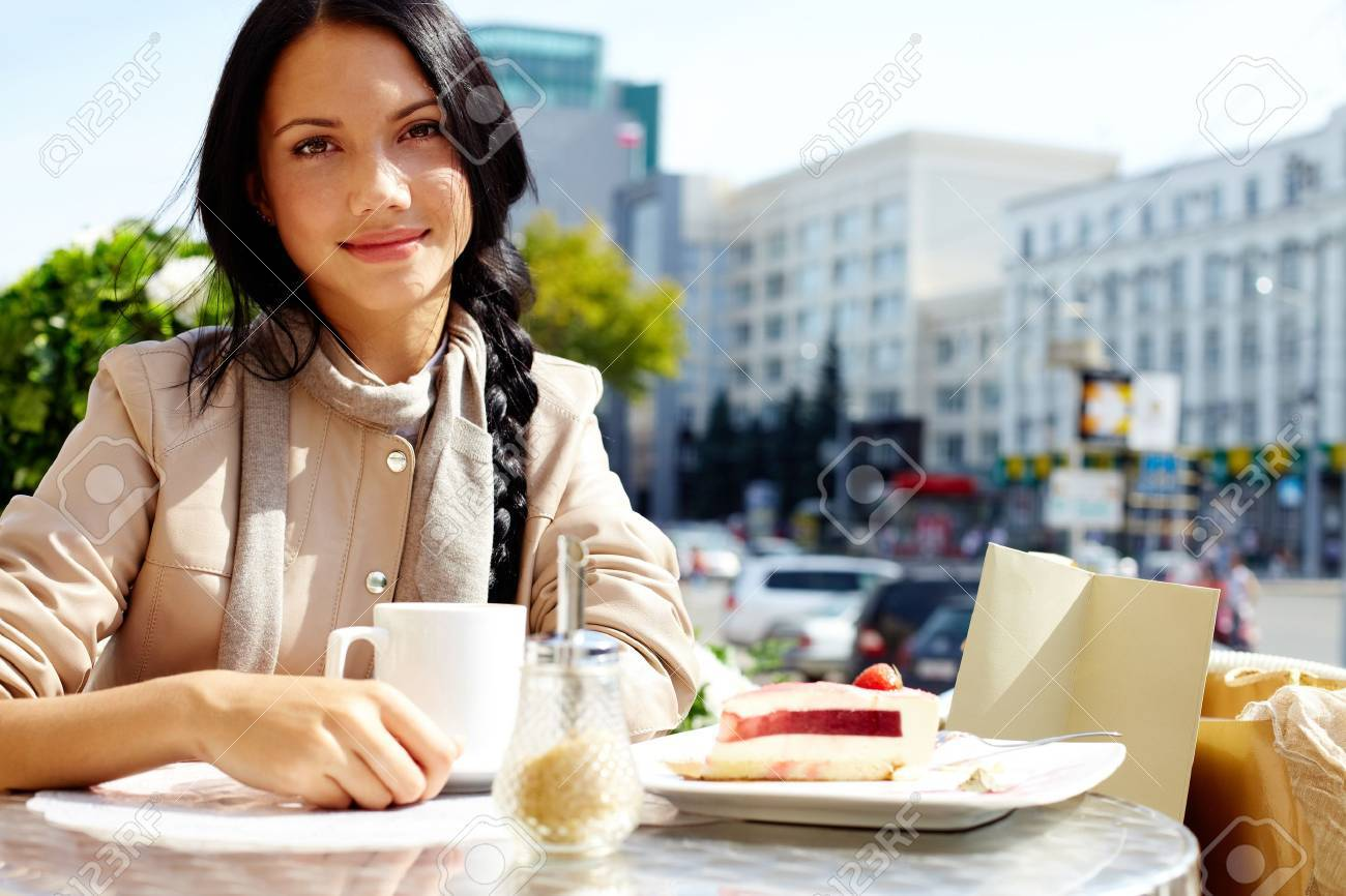 Image of happy female in open air cafe looking at camera in urban environment Stock Photo - 10546584